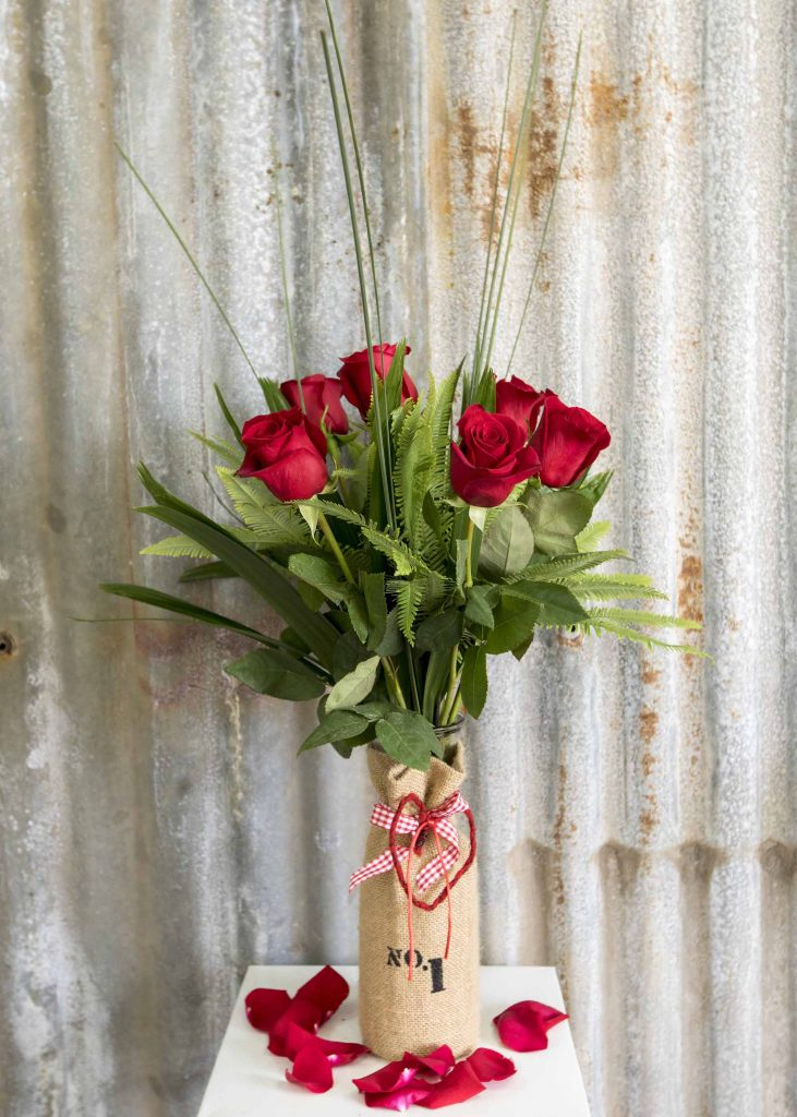 6 Red roses in Hessian covered glass vase